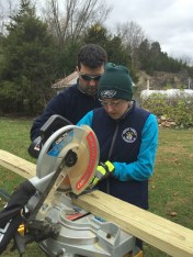 Rob Johnson showing his daughter how to use a chop saw