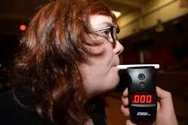 girl blowing into breathalyzer