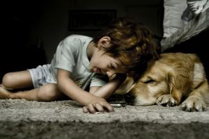 Young boy lays next to the family dog.
