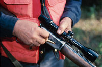Photo du bras d'un chasseur tenant son arme