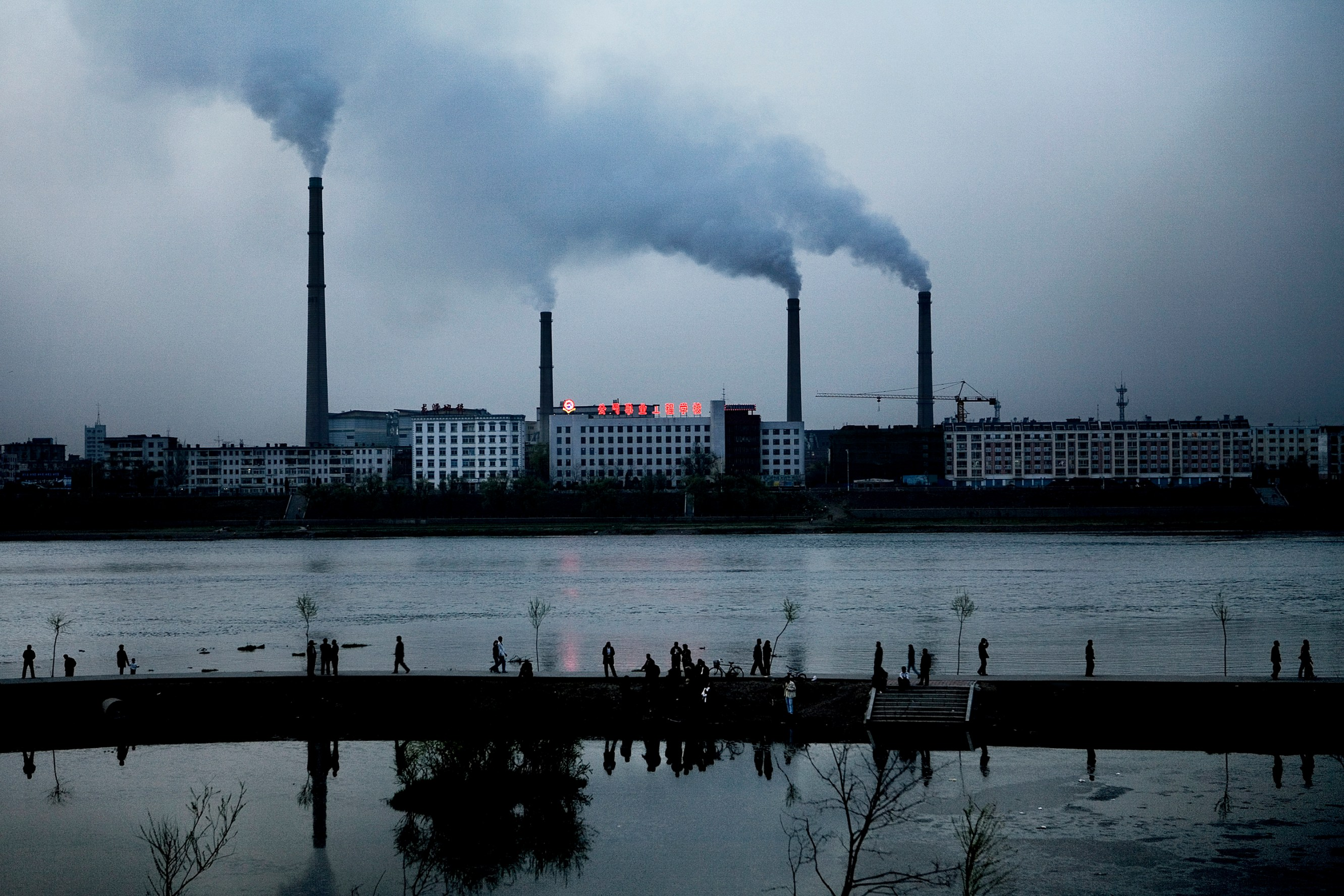 Thousands of citizens of Jilin stroll along the Songhua River on a Sunday evening. In Jilin City, where a Petro China chemical factory exploded last November, more than 200 factories lining the river pollutes the river and the air on a non-stop basis. Christian Als / GraziaNeri
