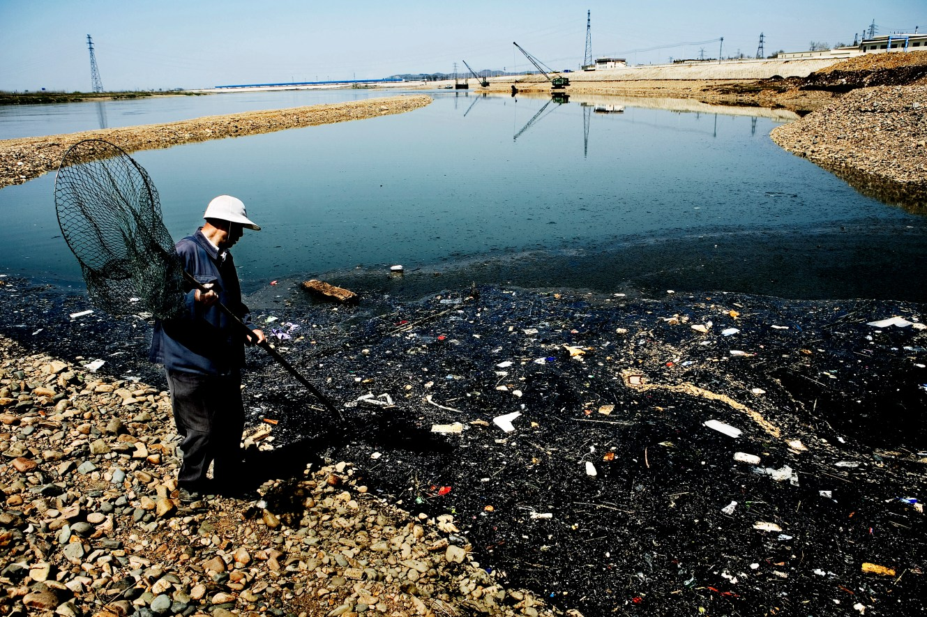 A local fisherman hunts for supper along the polluted Songhua River. Even though oil and garbage floats on the surface he got lucky soon after and landed a small fish in his net. Christian Als / GraziaNeri