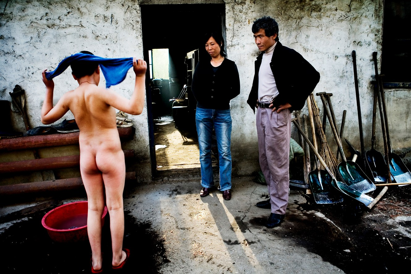 Outside their worn down house, 13-year-old Jiang has just finished taking a bath in water fetched directly from the Songhua River. Since the chemical disaster, the family often gets severe diarrhoea and full body rashes after wearing freshly washed clothes. Christian Als / GraziaNeri