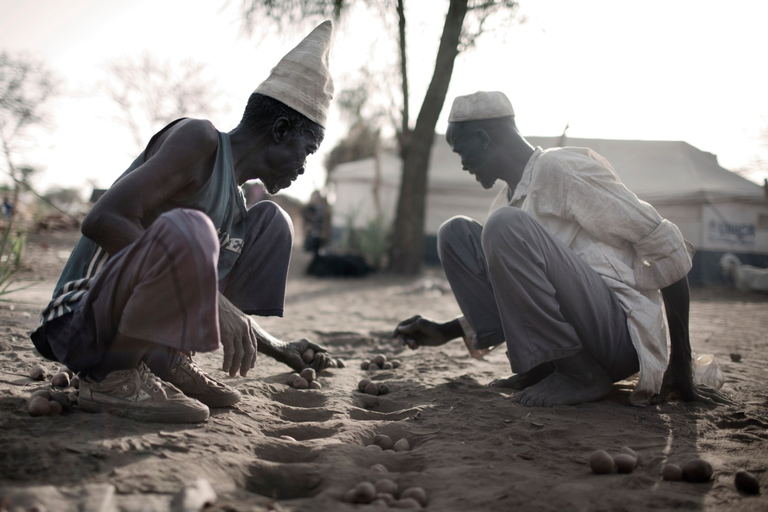 Two elderly men playing a game, possibly Mancala, on the dusty ground in Doro refugee camp.