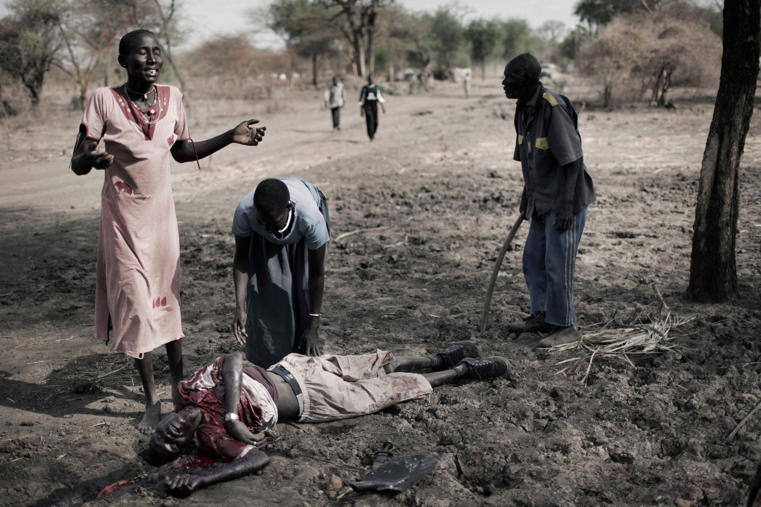 The wife of a man stabbed to death with a spear, cries beside his bloodied corpse in Doro refugee camp. The death was the result of an inter-tribal conflict, one of many assaults and murders occuring in the refugee camps of South Sudan.