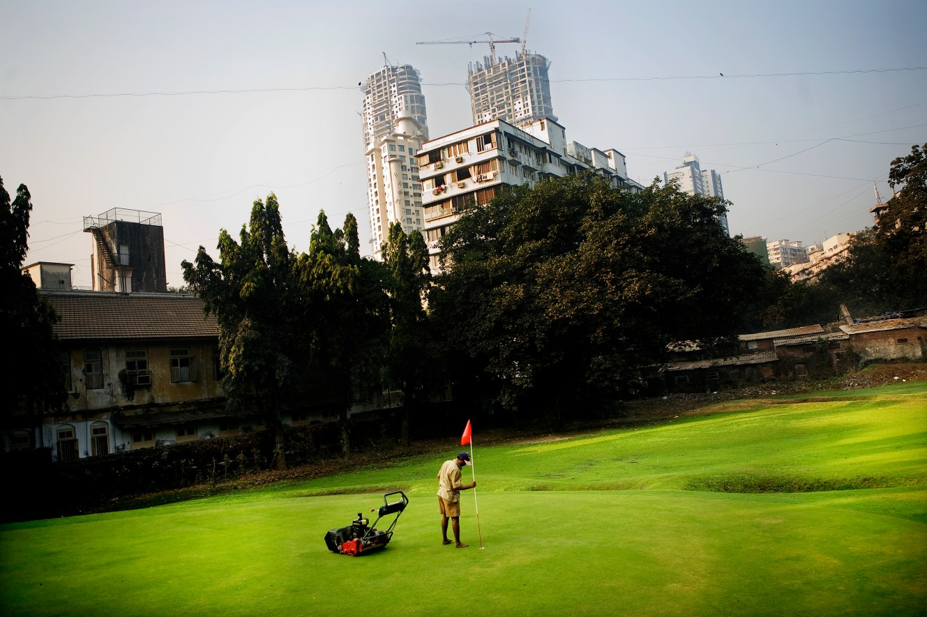 The urban extremes can be hard to take in the Indian mega cities. A new golf course has sprung up in downtown Mumbai, while new skyscrapers are being built in the background.