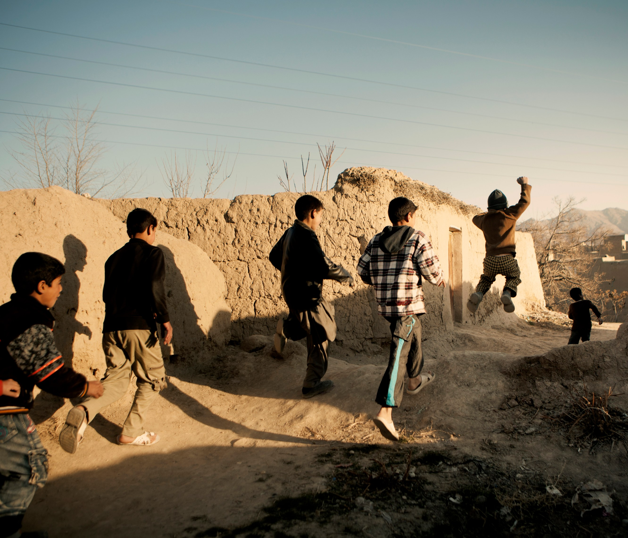 A group of boys leaping and jumping as they run through a back lane in a mud brick village. In June 2011, President Obama announced his plan to begin the withdrawal of US troops from Afghanistan, but there is currently no end date for the war in the troubled country. Helmand is the largest province in Afghanistan, and the heart of the war against terror. Commanders on the ground have described the situation as the most brutal conflict the British Army has been involved in since the Korean War. Much of the fighting between NATO and Taliban forces is taking place in this province and Helmand is a true Taliban stronghold. The Helmand River flows through the mainly desert region. With these images I am trying to show a softer side to this troubled area of Afghanistan.