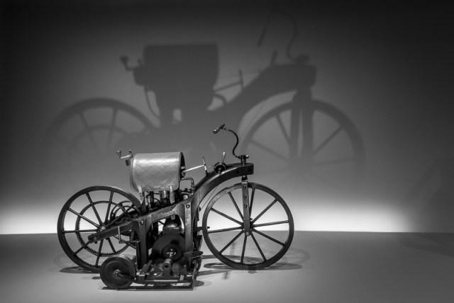 """Der Reitwagen (1885, hier ein Nachbau) steht, ist das älteste Fahrzeug mit Benzinmotor (5 PS (0,4 kW), Höchstgeschwindigkeit 12 km/h) und das erste """"Motorrad"""" der Welt."""