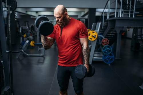 athlete-doing-exercise-with-dumbbells-in-gym-7FYAZM2-min.jpg