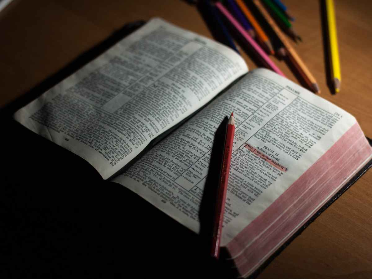 pink pencil on open bible page and pink