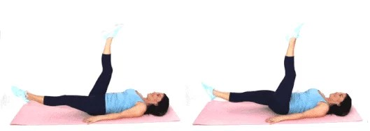 Christina Carlyle doing a scissor kick ab exercise at home