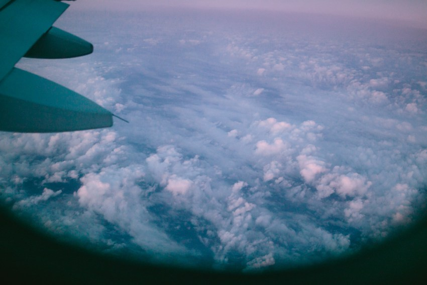 Blue and purple skies with clouds below an airplane wing