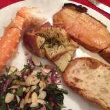 An AMAZING dinner of pork, crab legs, rosemary potatoes, and salad