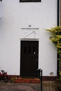 Relief ovanför radhusdörr. / Relief above row house entrance.