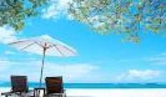 A photo of a pristine beach, two chairs, and an umbrella.