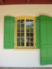 Casement windows with a segmental arched head in Louisiana's Pitot House bring in air cooled in the shade of the gallerie