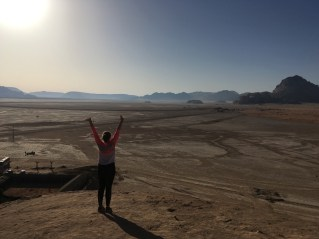 Camel race track in distance - me on top of a cliff in Wadi Rum