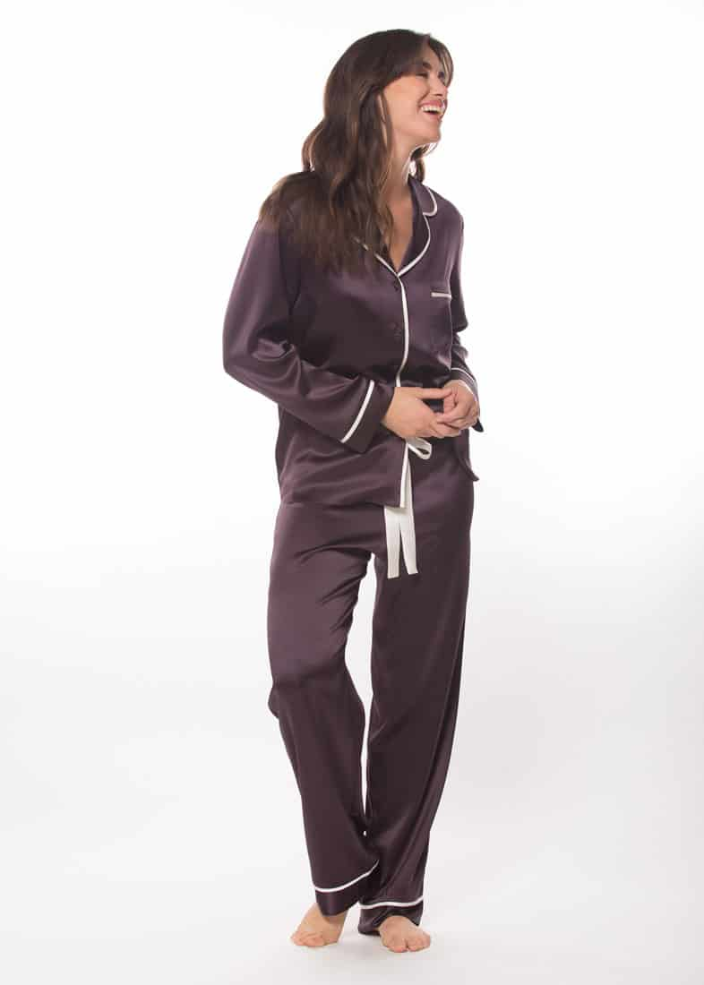 A silk purple pajama set with white lining is worn by a women