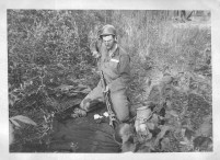 """Boyd Shaner cleaning his rifle in bivouac. It is just in front of our tent, but you can't see it."""
