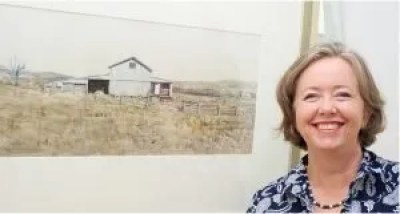 """Christine Porter, painter, in front of her woolshed watercolour """"Shed from the north"""""""