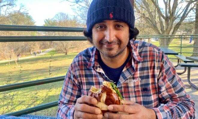 Enjoying a vegan burger at a park.