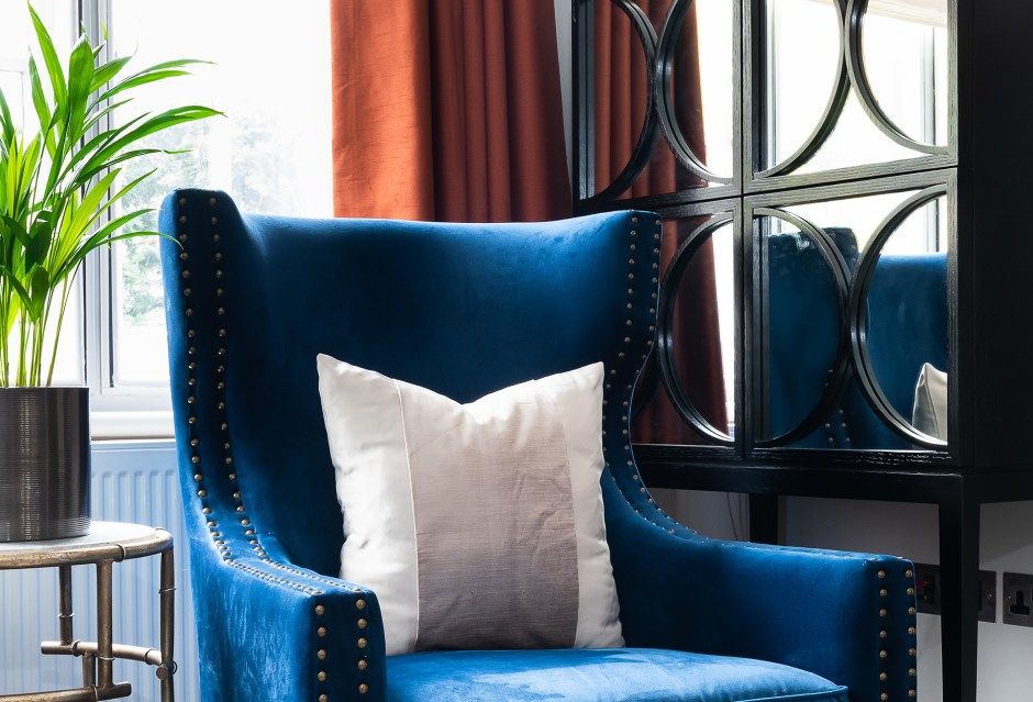 Family room_Living Room_blue and copper colour scheme_Richmond_London_Christine Tse Interiors_London Interior Designer_North London Interior Designer_Copper Curtains_ brown faux leather ottoman with storage_ Blue wingback chair_ mirrored brown wine cabinet storage