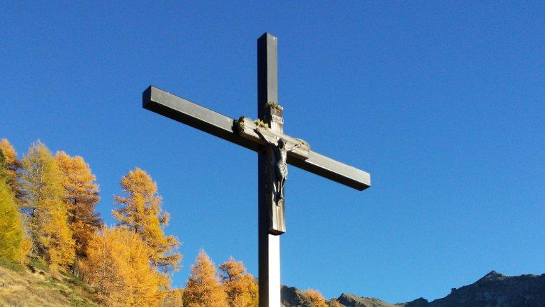 Kreuz mit Jesus-Figur in den Bergen