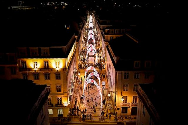 People walk past a street with traditional Christmas lights that were inaugurated in downtown Lisbon, Portugal