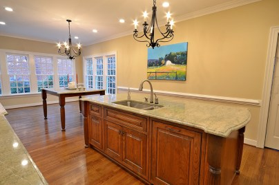 Large island and counter-height table function as prepping, serving, and dining areas