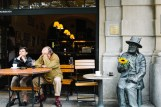 couple in cafe with statue next to them in krakow