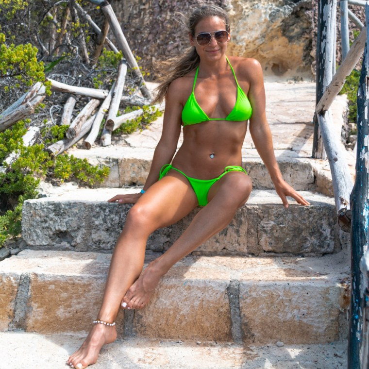 Model Corky, full body on a short stone staircase, wearing sunglasses and a neon green bikini. Photo by Christopher Keelty.