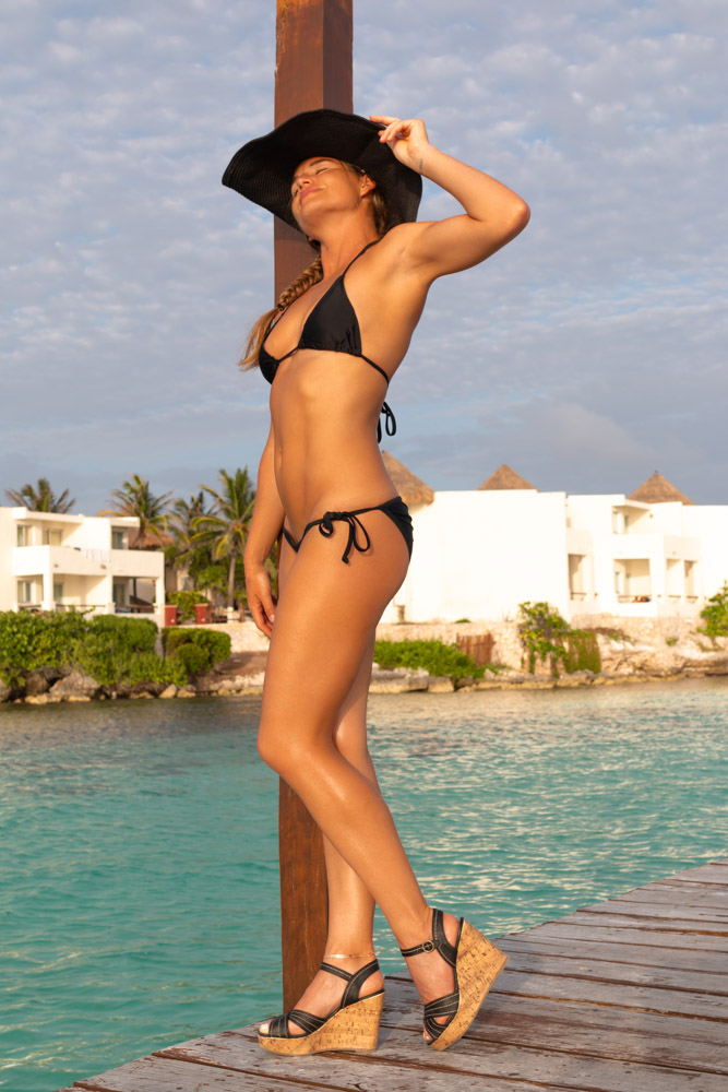 Corky leans against a post wearing a black bikini and beach hat, in Isla Mujeres, Mexico. Photo by Christopher Keelty