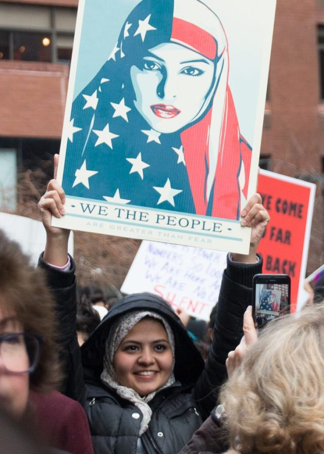 """A young woman in a headscarf at the New York City Women's March holds up Shepard Fairey's """"WE THE PEOPLE"""" poster featuring a woman in an American flag headscarf."""