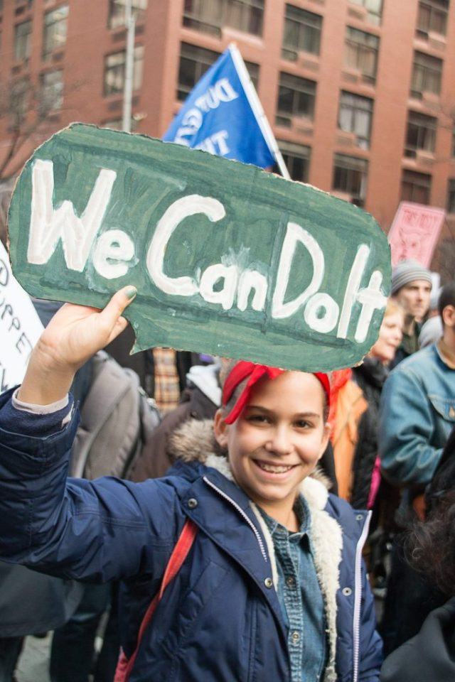 """A young woman, dressed in costume as the famous """"We Can Do It!"""" poster at the New York City Women's March"""