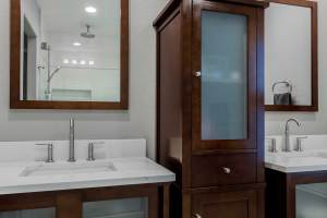 Transitional vanity with linen cabinet and marble-look quartz counterts, undermount sink and Santec faucets.