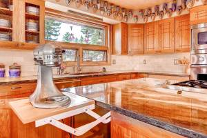 Cherry and oak custom kitchen cabinetry in Denver, CO with integrated appliance shelves in island and quartzite countertops.