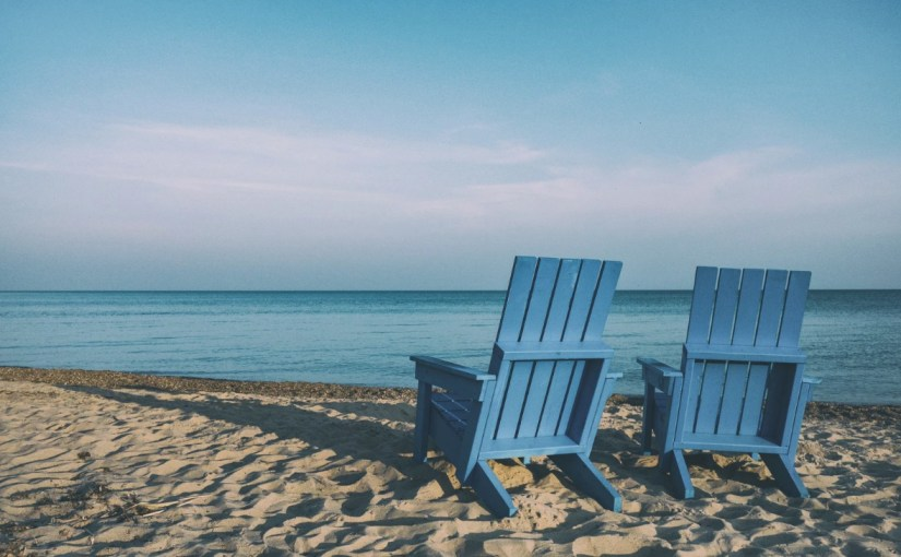 Two blue, wooden Adirondack chairs on a beach