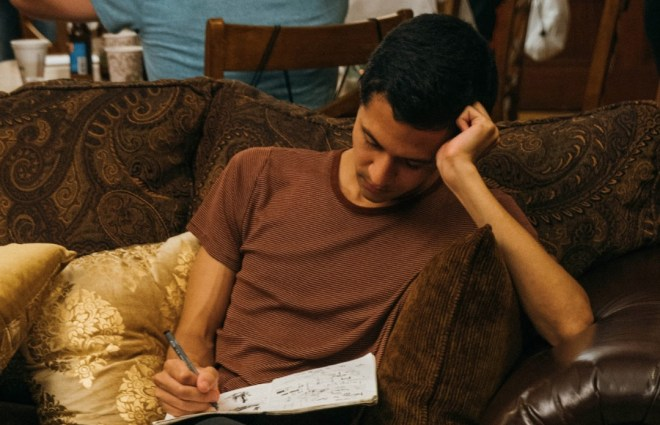 Austin writing in his notepad, looking introspective