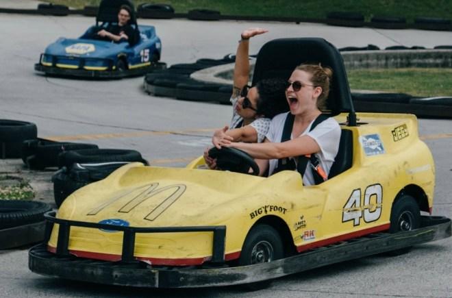 Julie in a yellow go-kart smiling next to teammate Alisha Miranda