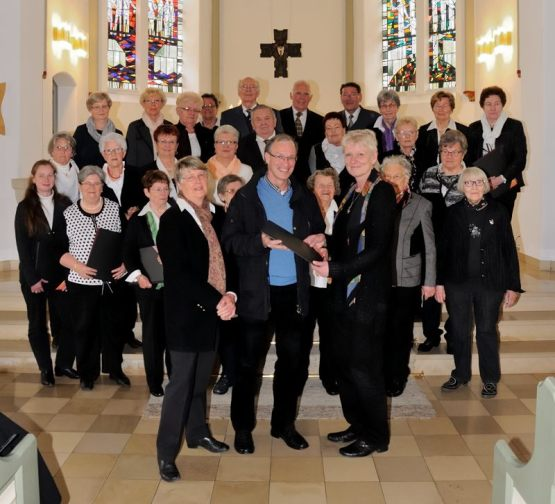 Ilse Pohl-Ringkamp und Ingo Engeln vom Förderkreis überreichen Chorleiterin Kirsten Gernd die neuen Chormappen.