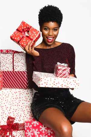 woman wearing maroon long sleeved shirt and black shorts holding gift boxes