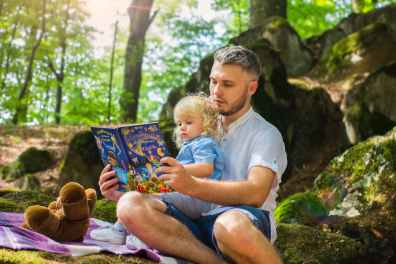 photo of man and child reading book during daytime