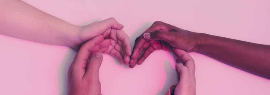 human hands forming heart on white surface
