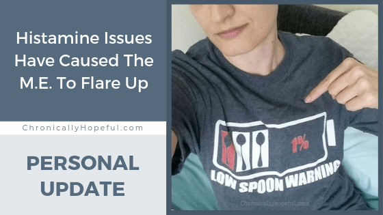 """Char is pointing to her shirt which shows an empty battery with the words """"low spoon warning"""" on it. Title reads: Histamine issues have caused the M.E. to flare up. personal update."""