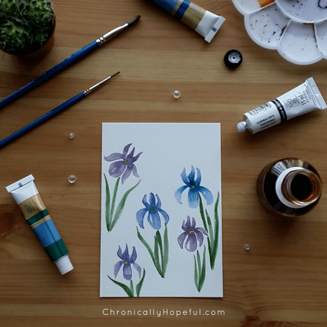 Blue and purple watercolour itises on a card, paints and brushes scattered on table around it.