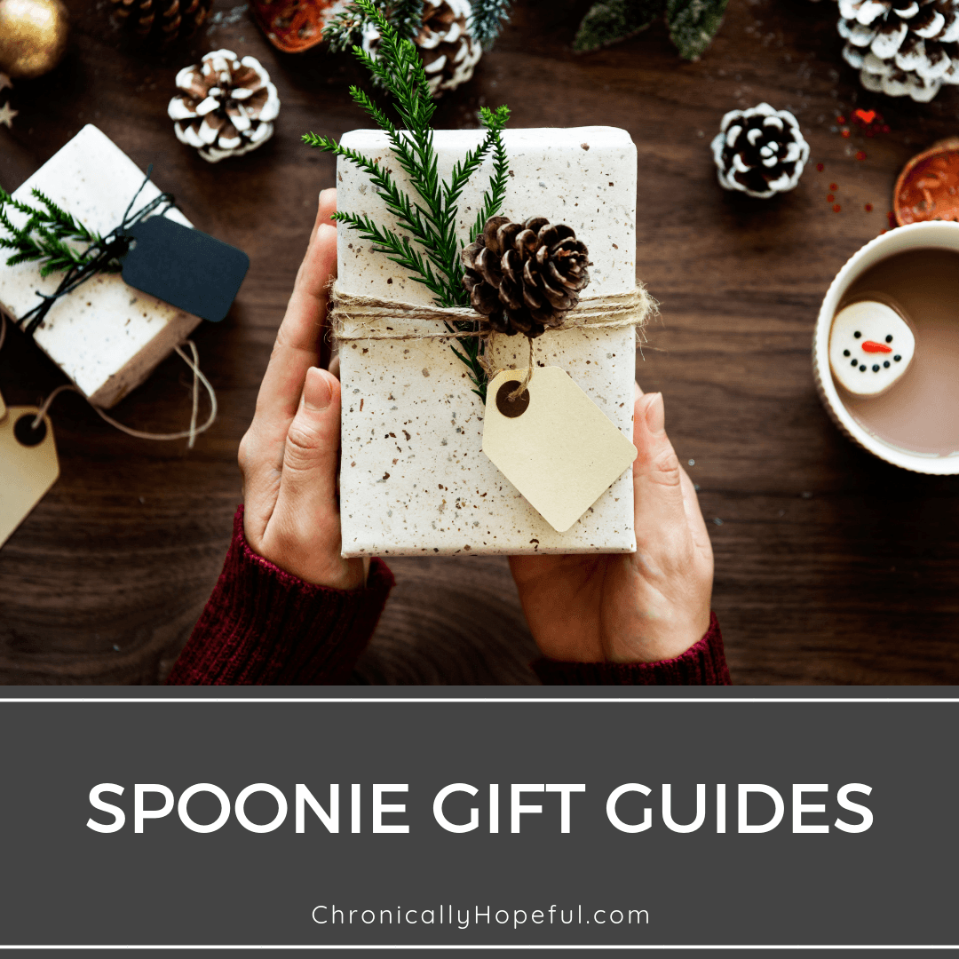 hands holding a wrapped christmas present decorated with pine cones and string. mug of hot chocolate on the right, more pine cones on the table in background. Captions says Spoonie Gift Guides
