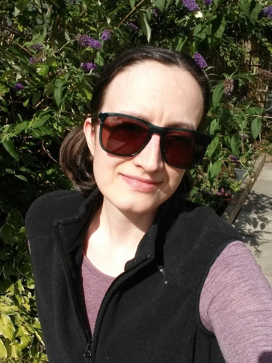 im walking in the garden, wearing sunglasses and a purple top.