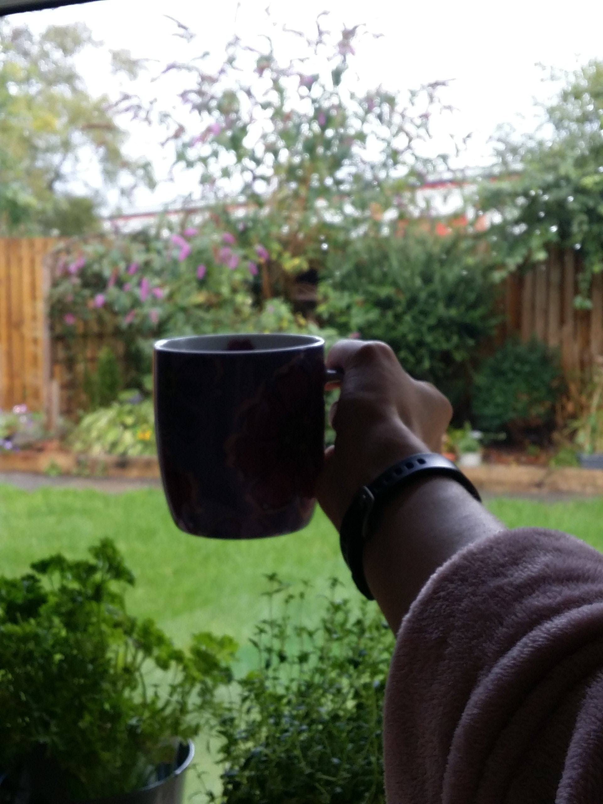 holding up a mug of coffee in front of a window overlooking a very green garden
