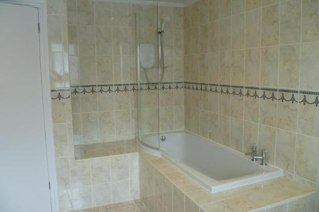 a large bathroom with a shower over the tub, walls and floors tiled with cream tiles.