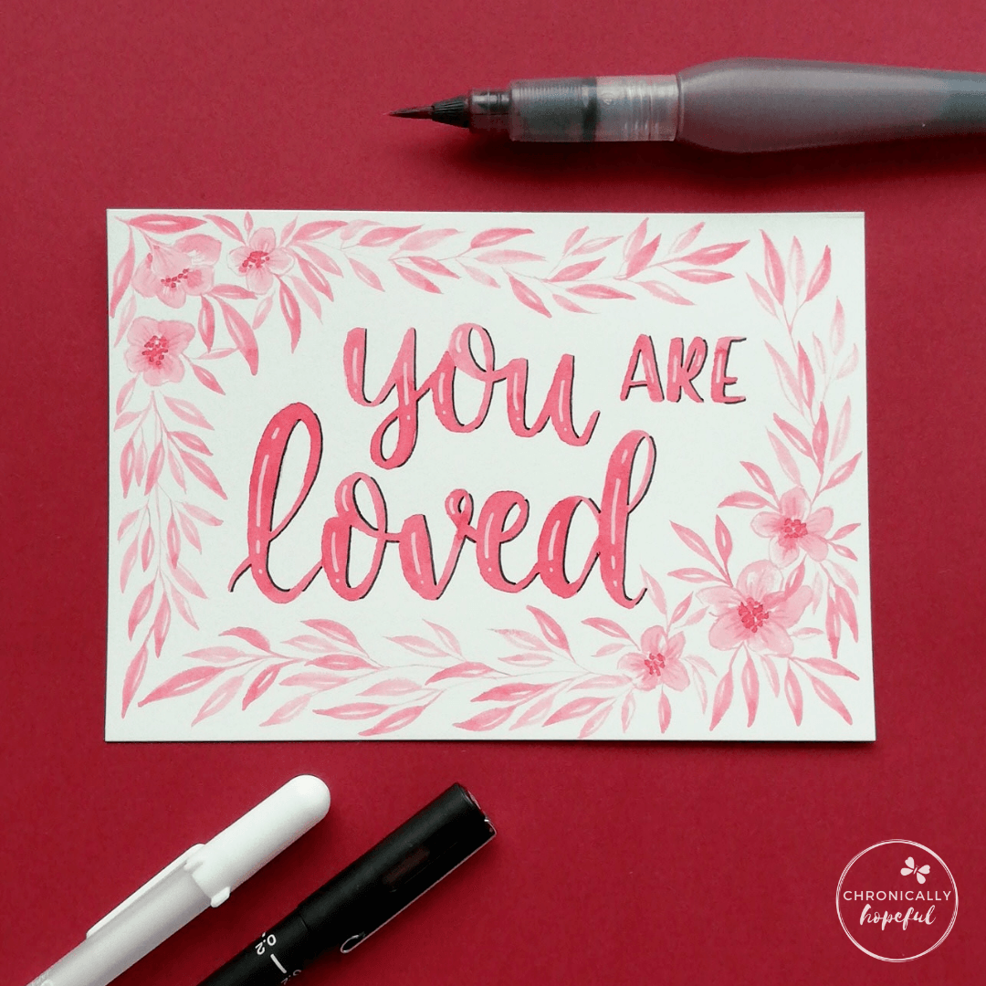 You Are Loved, watercolour lettering with botanical frame, pink paint on white card, Paint brush and pens on the table around the card.